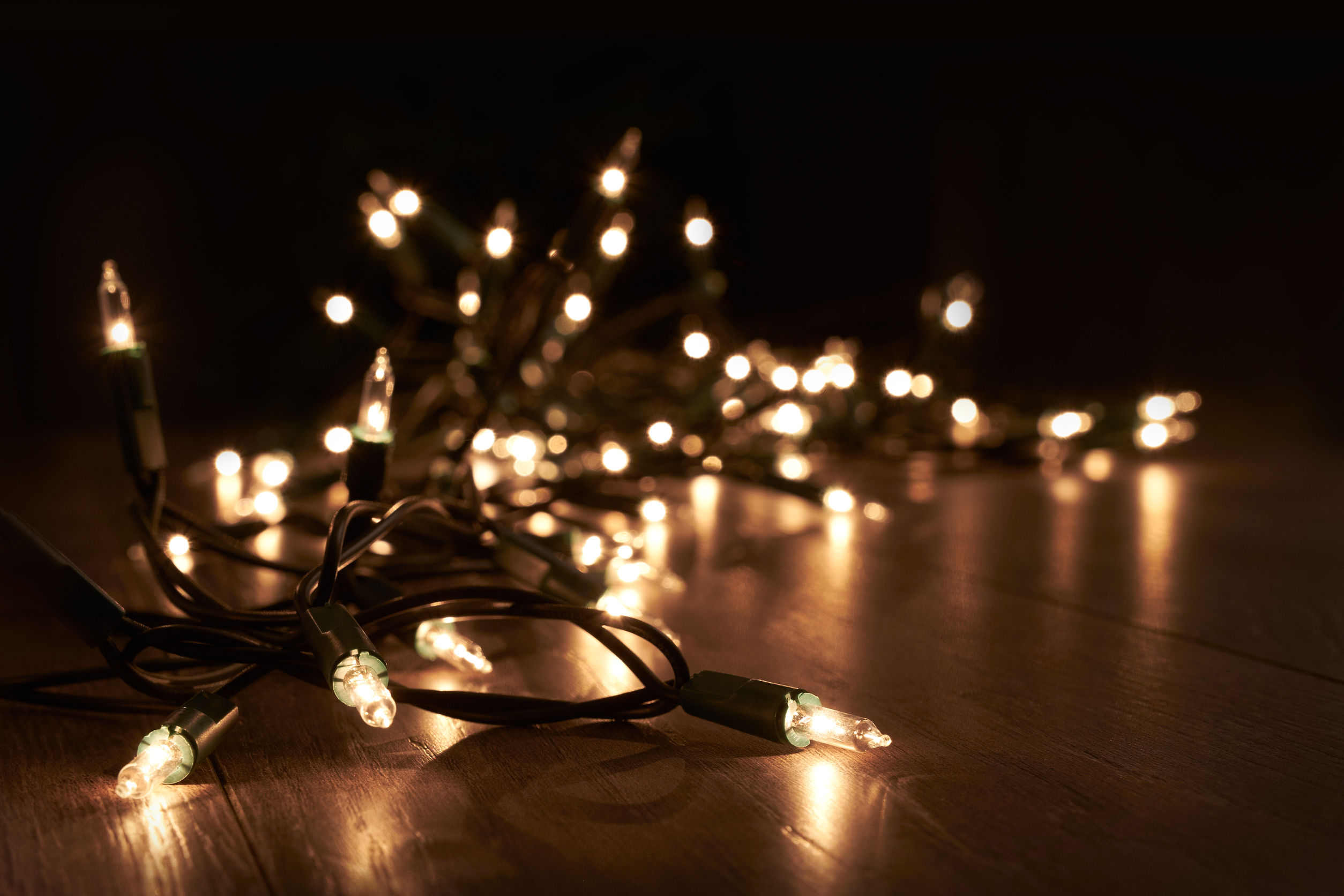 Traditional Christmas Tree lights lying on a wooden floor
